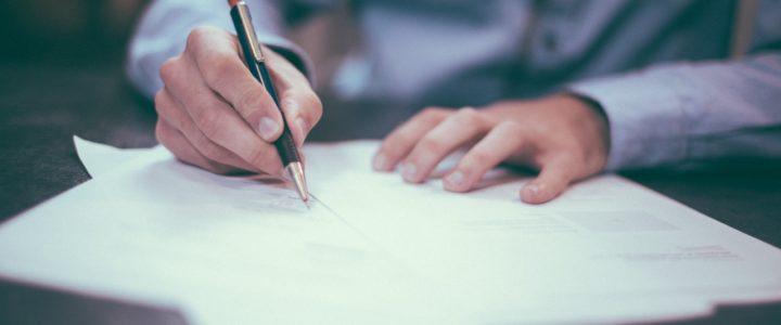 Zbliżenie na dłonie mężczyzny podpisującego dokumenty długopisem